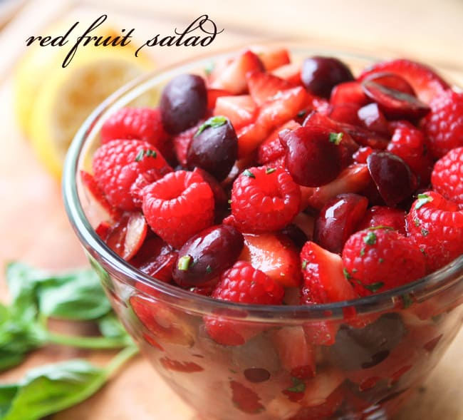 Bowl of red fruit salad with basil and squeezed lemons in the background