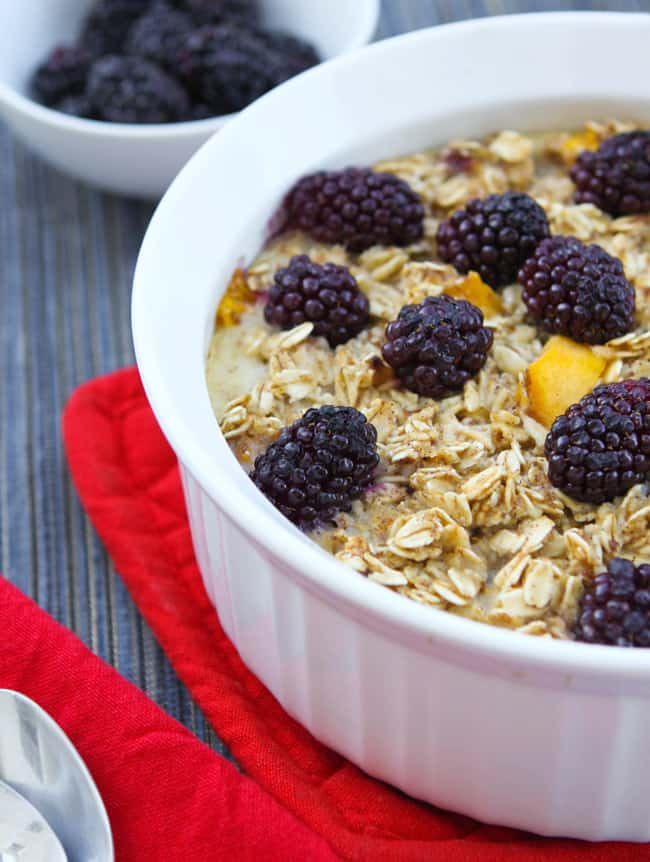 Partial view of healthy baked oatmeal in a casserole dish with whole blackberries and peach chunks on top.