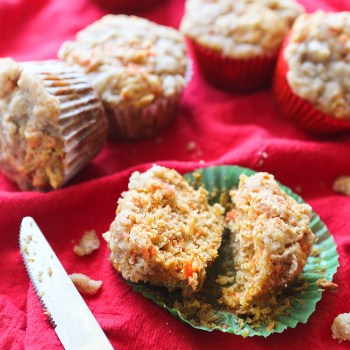 an apple carrot cake muffin split in half on a muffin wrapper with a butter knife next to it