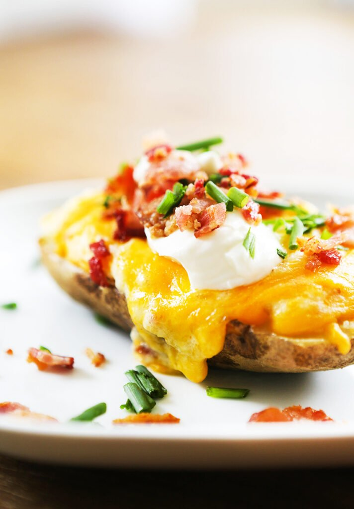twice baked potatoes on a serving plate with cheese oozing down sides