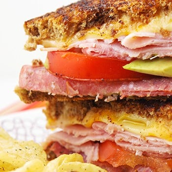 Close up shot of a leftover lunch meat grilled cheese sandwich cut in half and stacked on top of one another with chips on the side.