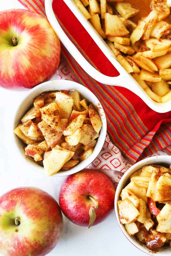 looking down into two serving bowls filled with baked apples and cinnamon