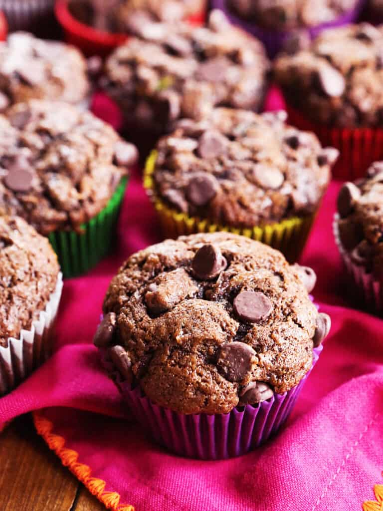 Double chocolate zucchini muffins placed on top of a magenta colored cloth.
