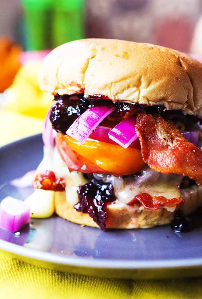 Burger topped with peaches, red onions, jam and bacon