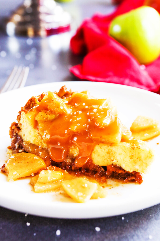 slice of salted caramel cheesecake with apples on top and caramel drizzled over the slice sitting on a plate.