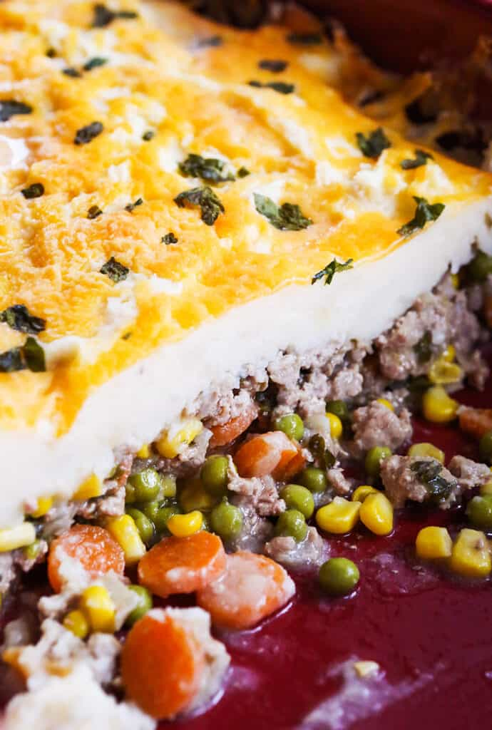 ground beef, carrots, peas and corn spilling out the bottom of a layer of mashed potatoes