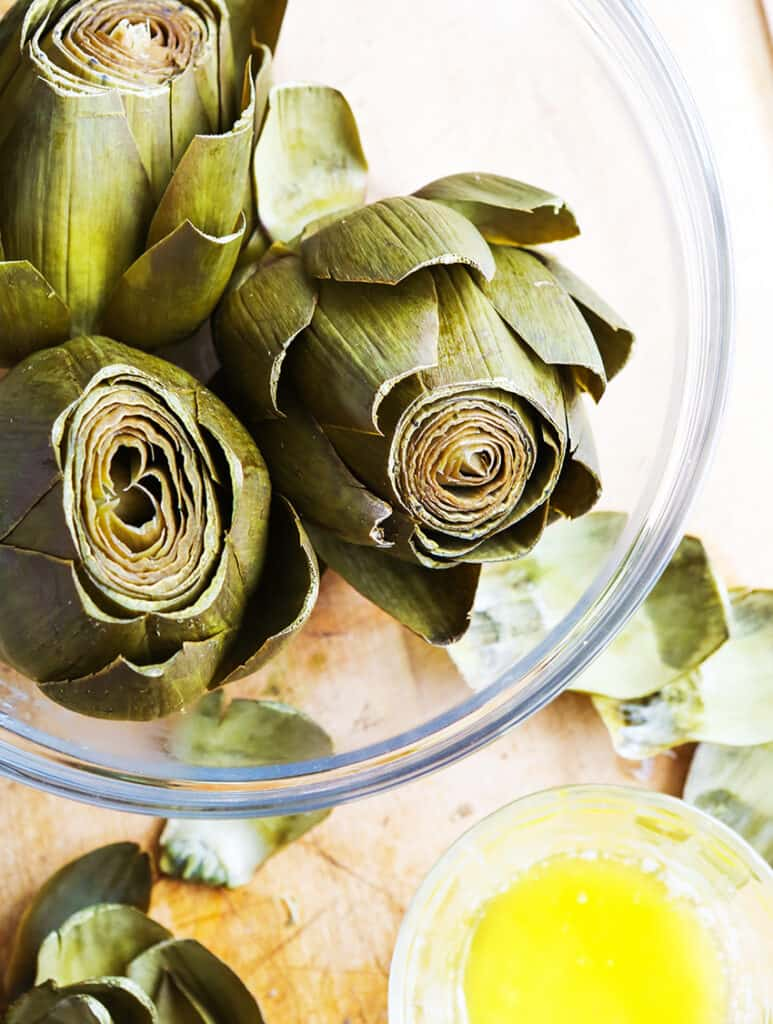 bowl full of steamed artichokes next to a cup of melted butter