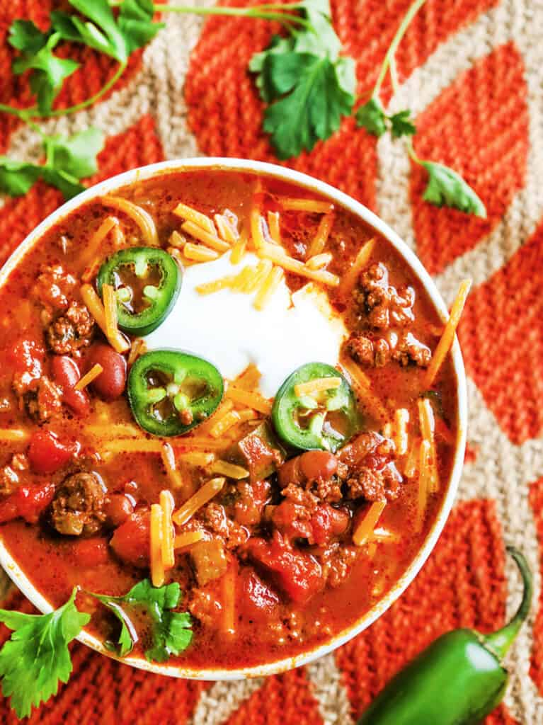 looking down into a bowl of chili with jalapeno slices, cheese and sour cream on top