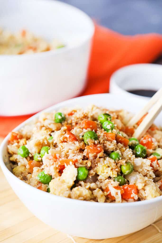 cauliflower fried rice with soy sauce next to it