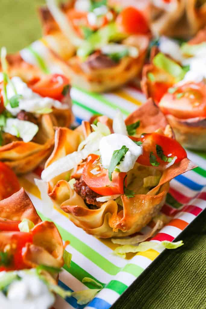 Taco cups filled with lettuce and tomatoes on a serving platter