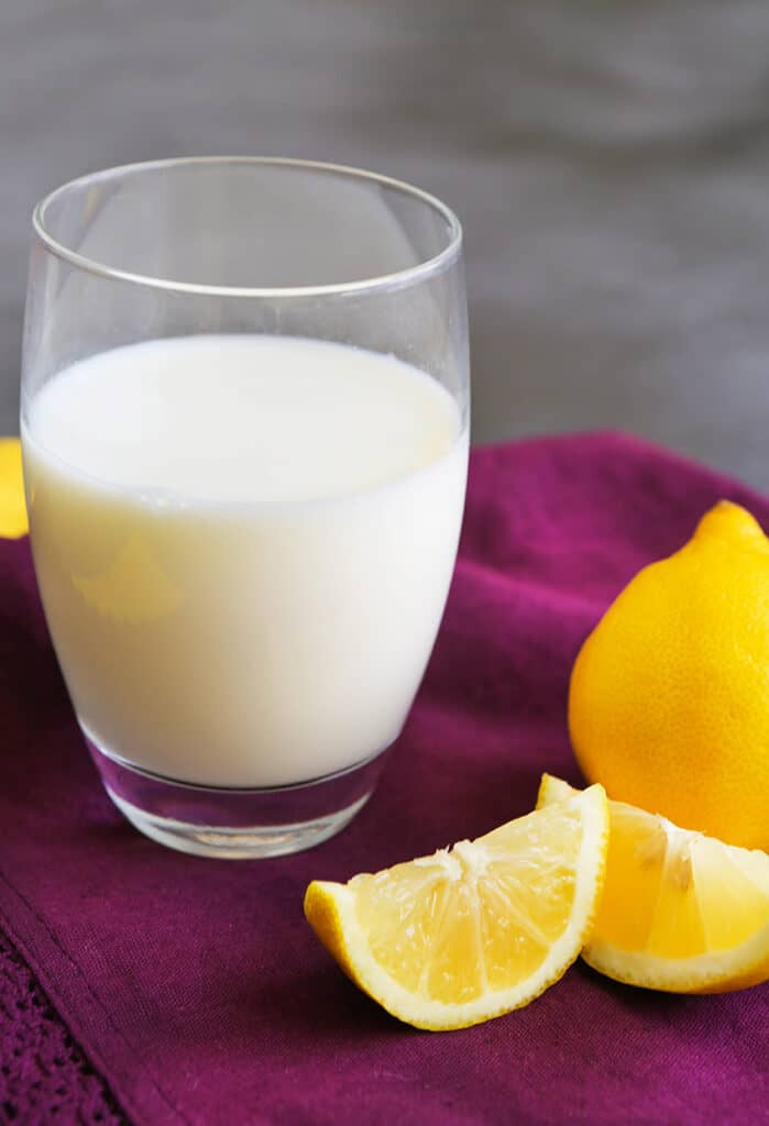 homemade buttermilk in a glass sitting next to lemon wedges