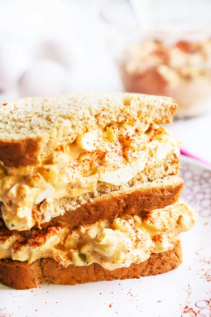 two halves of an egg salad sandwich sitting on top of one another on a plate