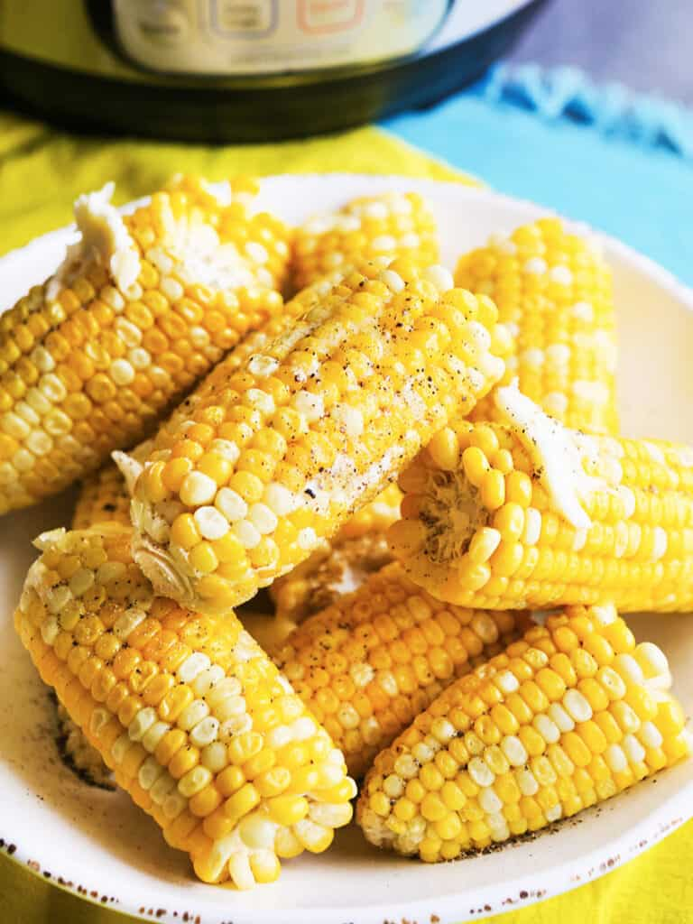 corn on the cob stacked on a serving plate with butter and pepper