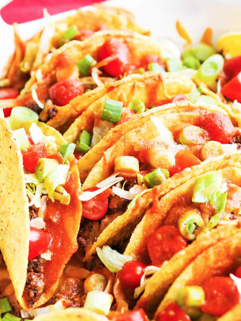 pan of tacos filled with toppings lined up and standing on end in a baking dish
