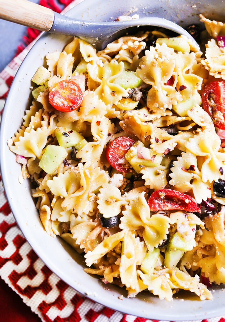 Mediterranean pasta salad ready to serve in a bowl with a serving spoon.