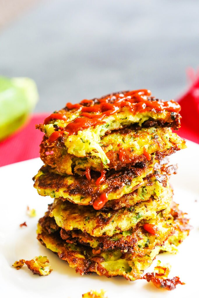 zucchini fritters topped on one another with ketchup drizzled on top