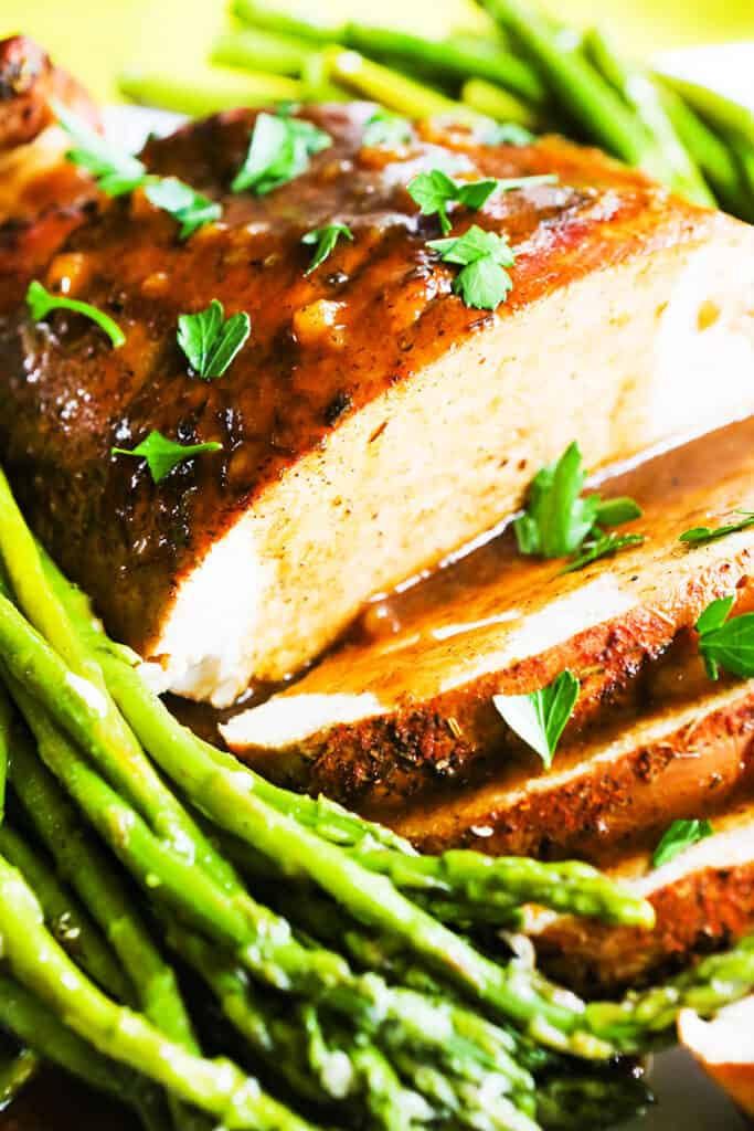 instant pot turkey breast sliced with gravy drizzled over it on a platter with a side of asparagus