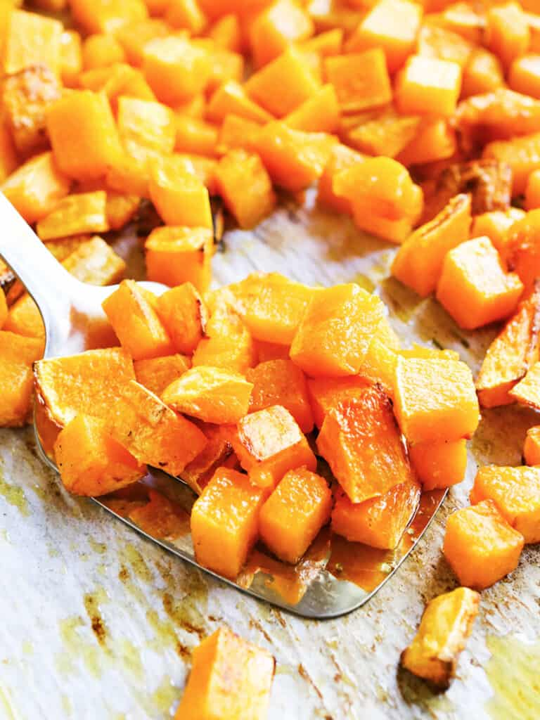baking sheet with a spoon scooped up full of roasted butternut squash