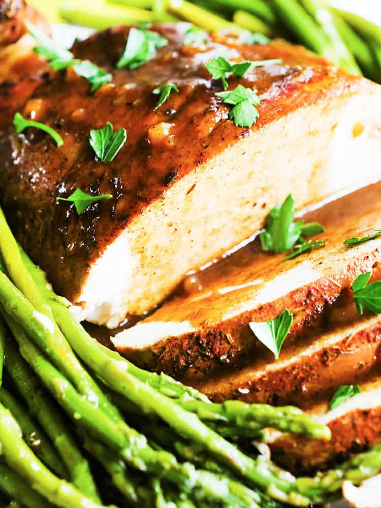 a turkey breast with several slices cut open and gravy poured over the top with asparagus on the side.