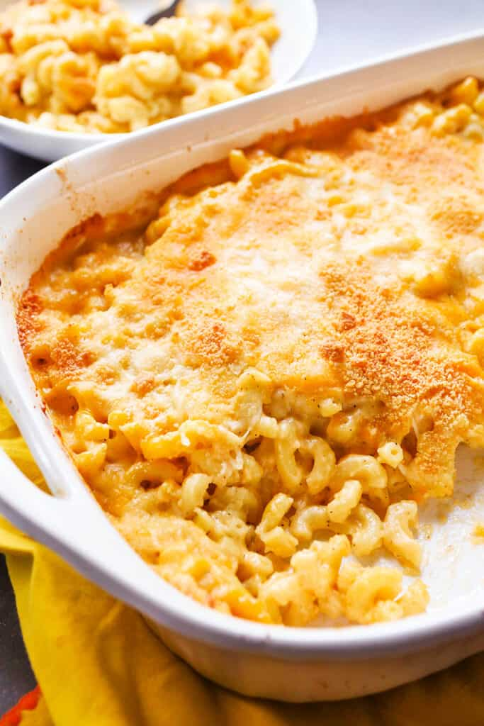 a serving dish of baked mac and cheese with a serving missing