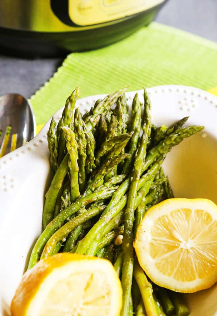 serving bowl with instant pot asparagus inside with 2 slices of lemons sitting on top