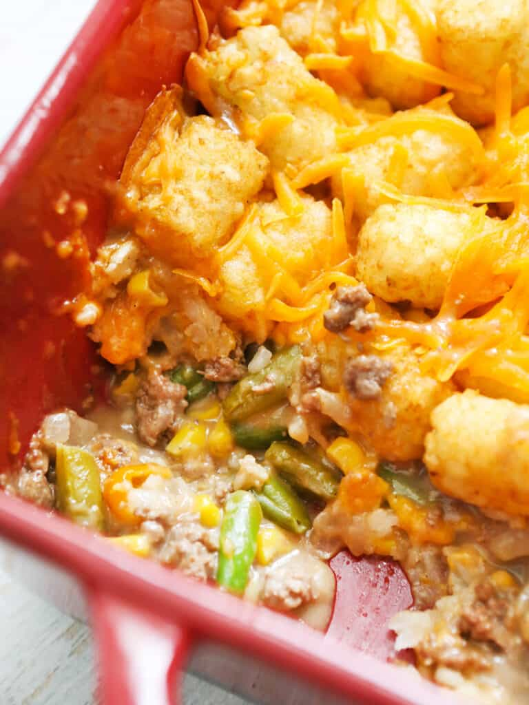cheesy tater tots with veggies and beef spilling out the bottom in a baking dish