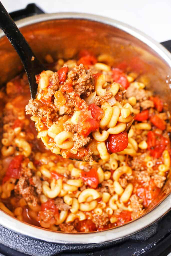 ladle full of cooked pasta, tomatoes and meat being lifted out of an Instant Pot