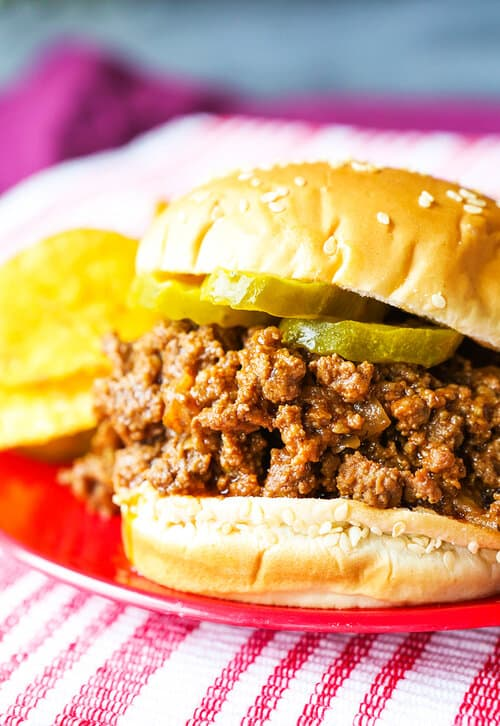 a sloppy joe on a bun sitting on a red plate with dill pickle chips sitting to the side