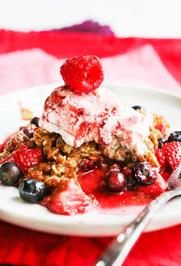 plate of berry crisp with a scoop of ice cream on top and a raspberry garnish