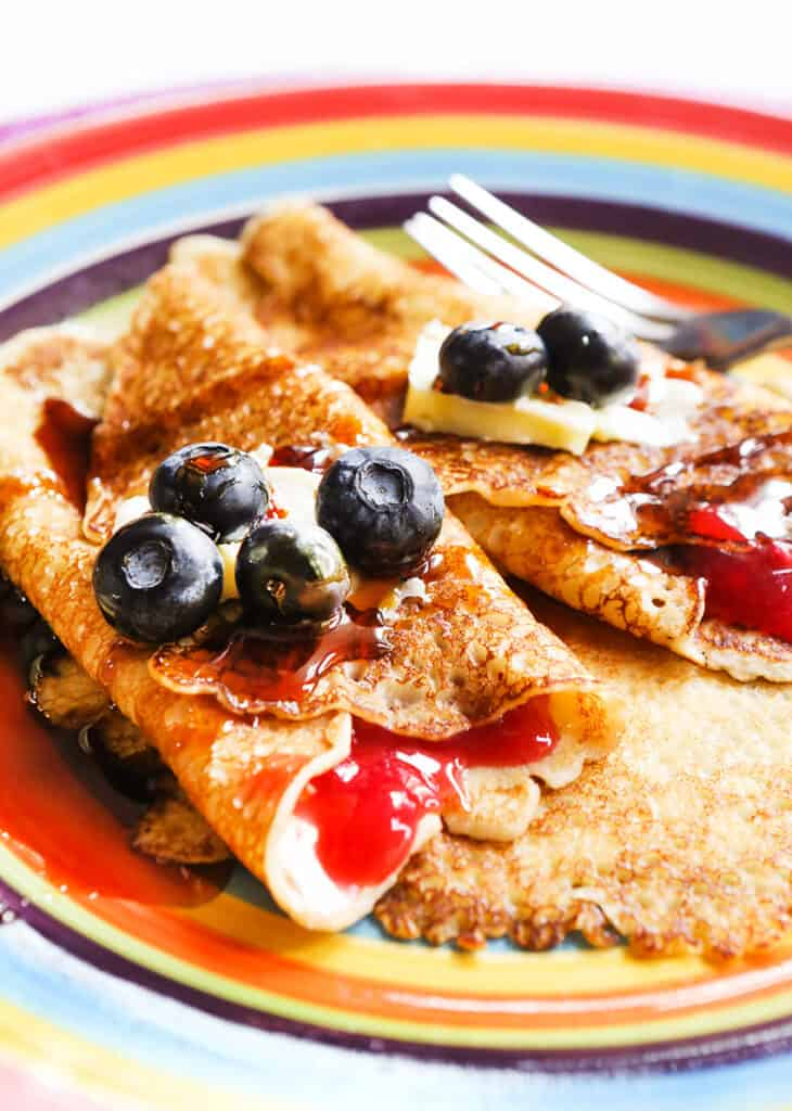 Several grandma's swedish pancakes folded in thirds with jam oozing out and blueberries  garnished on top.