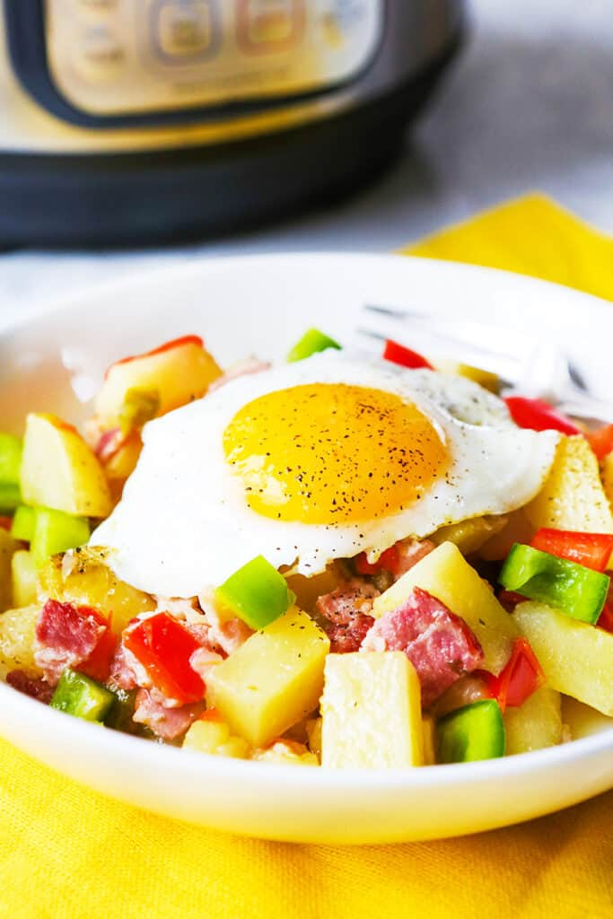 A bowl of instant pot breakfast potatoes with an egg sunny side up on top of it.