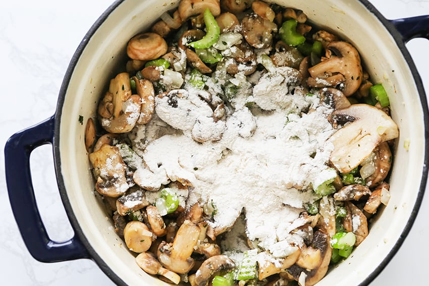 Flour sprinkled over mushroom mixture in Dutch oven
