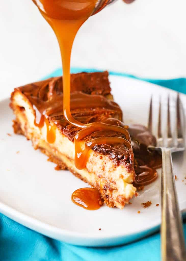 caramel sauce being poured over a slice of cheesecake