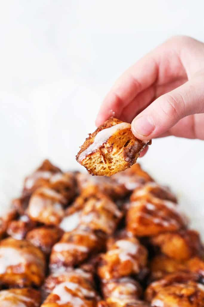 Hand holding a piece of monkey bread with icing