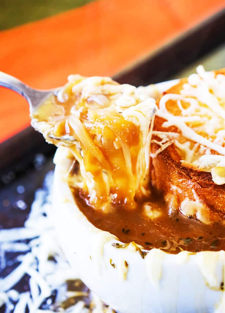 super cheesy spoonful of french onion soup being pulled out of bowl