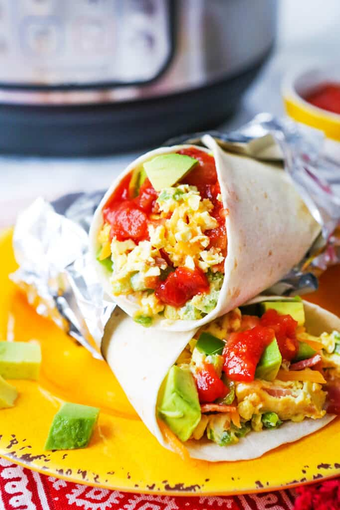 Two breakfast burritos stacked on top of each other on a plate in front of an Instant Pot.