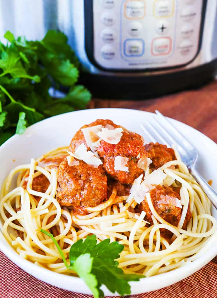 Heaping plate of spaghetti and meatballs next to Instant Pot