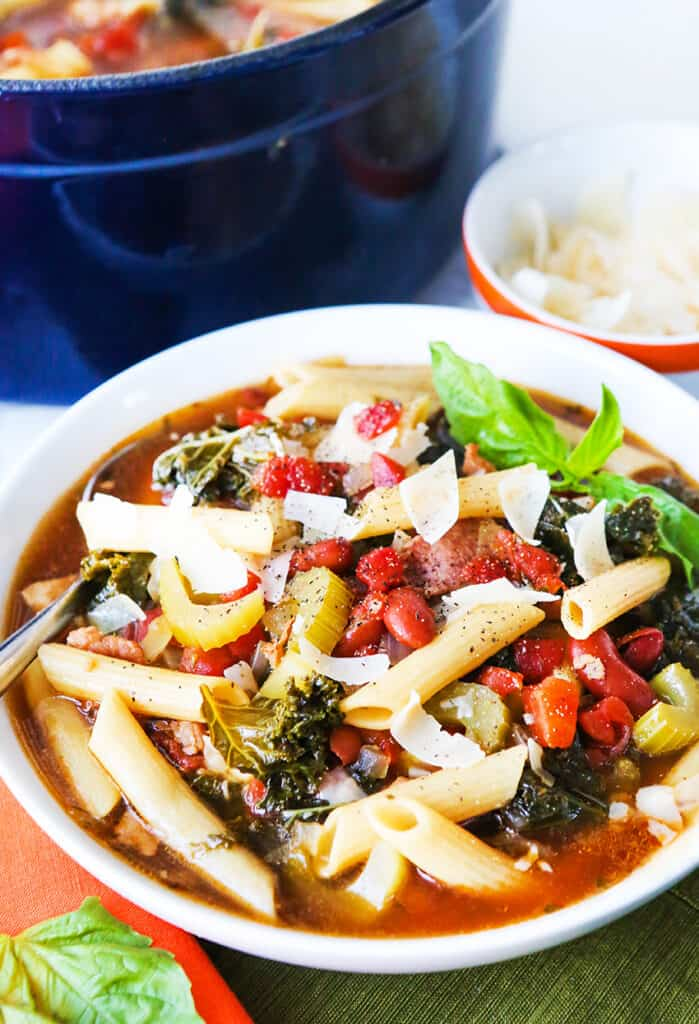 Bowl of minestrone soup sitting next to pot full