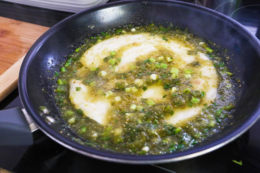 Salsa verde and green onions in skillet