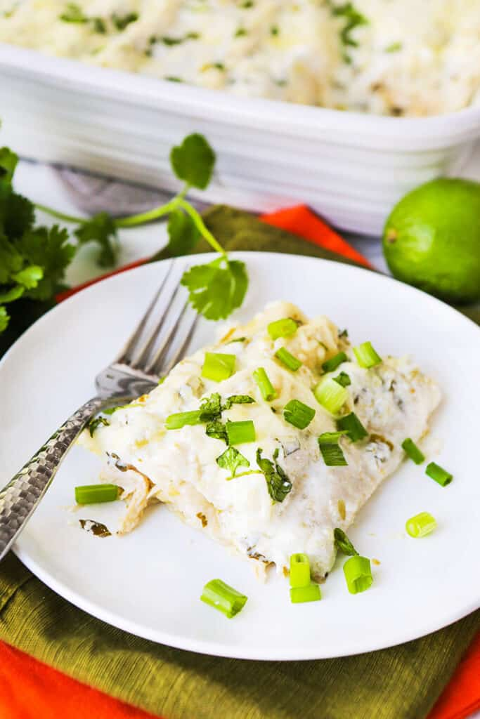 Serving of chicken enchiladas on plate next to baking dish