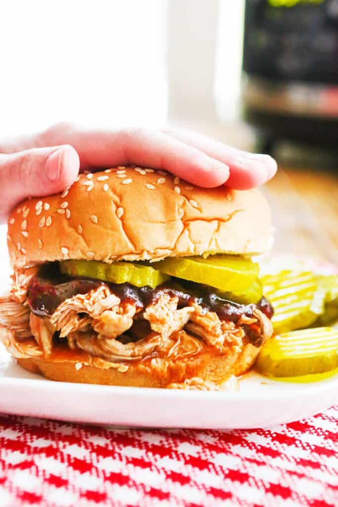 hand pressing down on top bun of pulled pork sandwich
