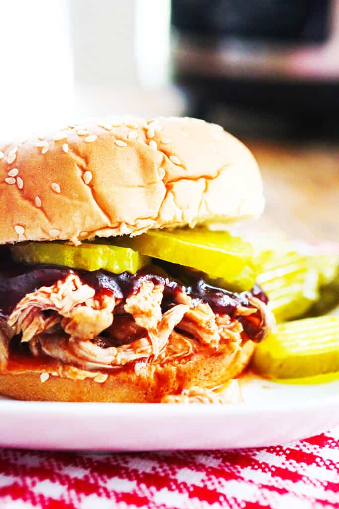 pickles sticking out of pulled pork sandwich next to Instant Pot
