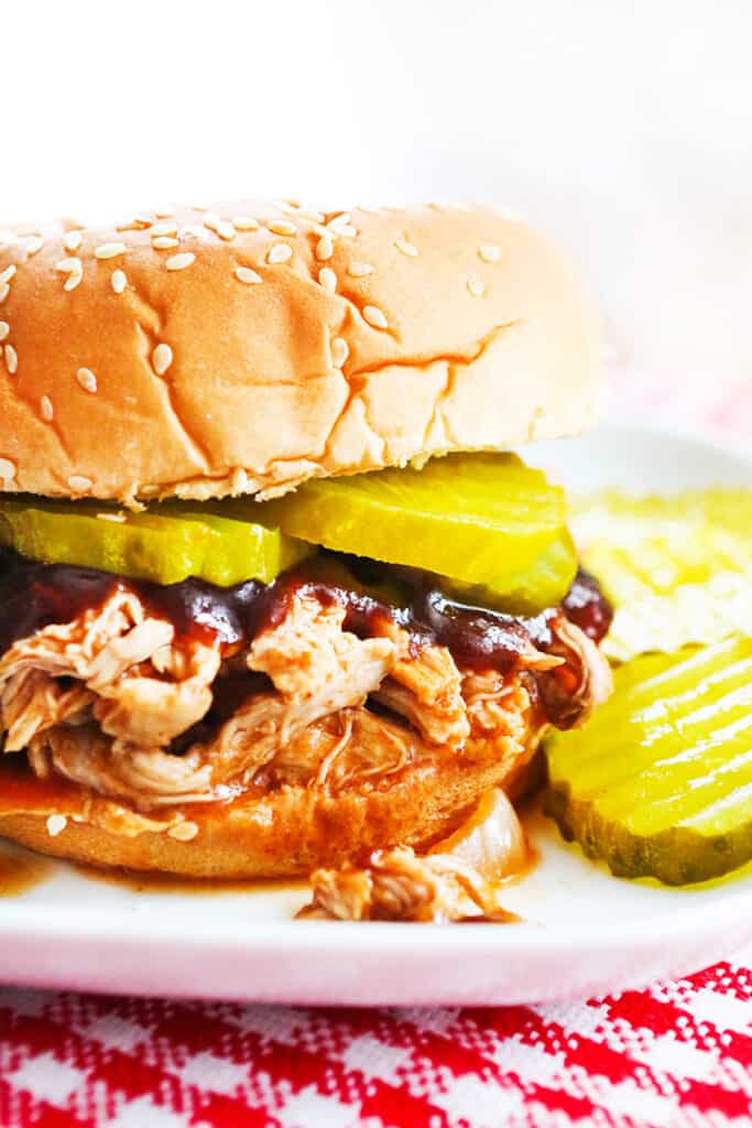 pulled pork on a sesame bun with pickles and bbq sauce sitting on a plate