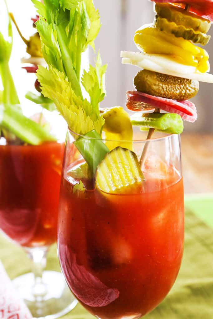 tall skewer of condiments coming out of a bloody mary