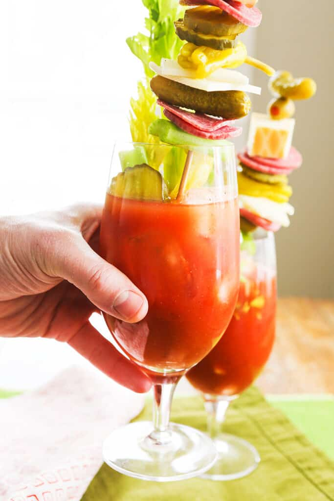 Hand holding a spicy bloody mary with a large garnish of pickles, salami, cheese and pepporoncini.