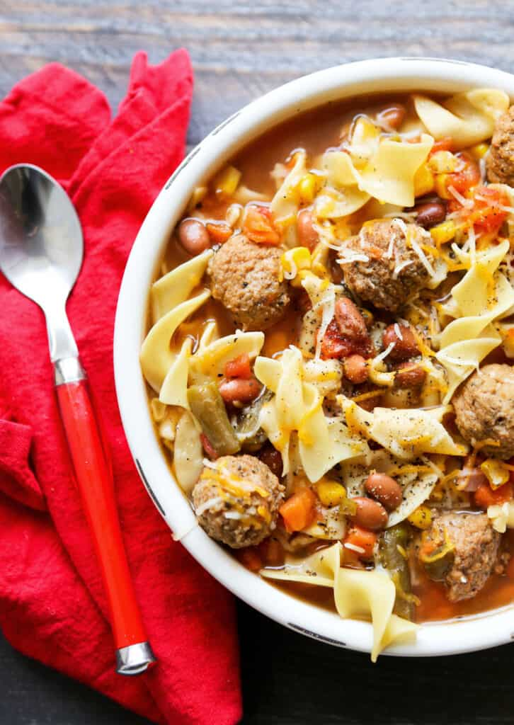 top view of a bowl of meatball soup with a spoon