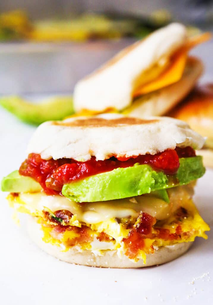 Breakfast sandwich with avocado slices and salsa