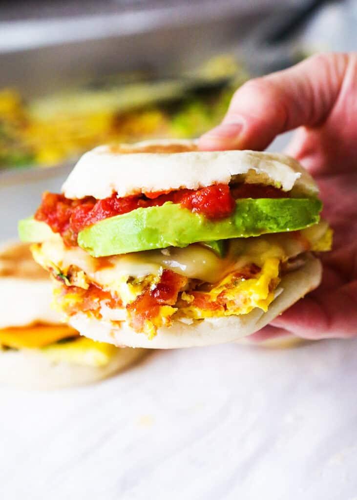 Hand holding breakfast sandwich dripping with salsa