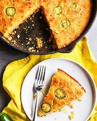 cast iron pan with a slice of jalapeno cornbread put on a plate next to it.