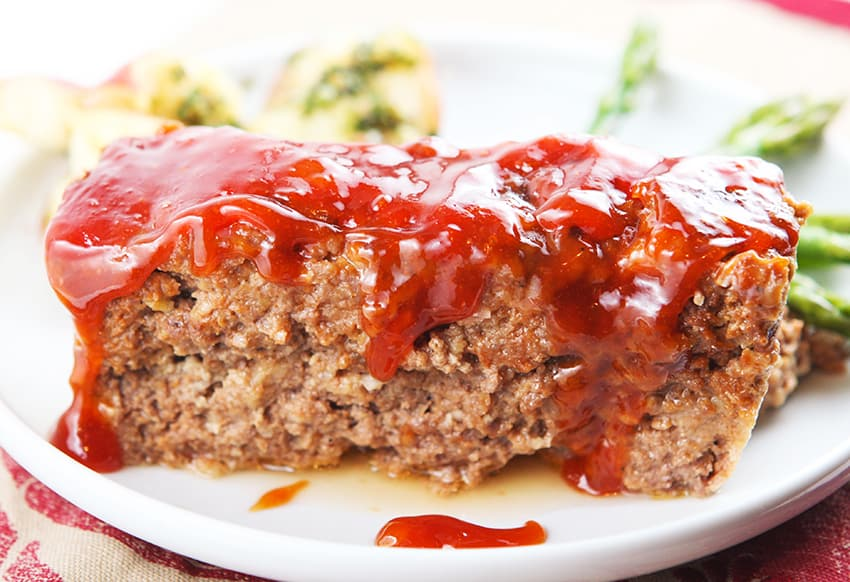 close up of a slice of meatloaf with sauce dripping down sides